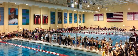 Swimmers stand on deck during the 400 Free Relay