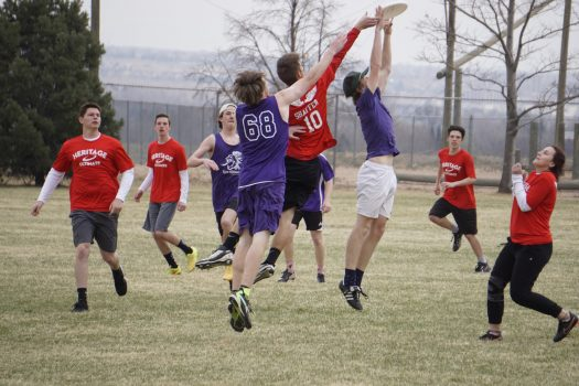 Juniors Will Dinneen and Ethan Schwarz leap for the disc