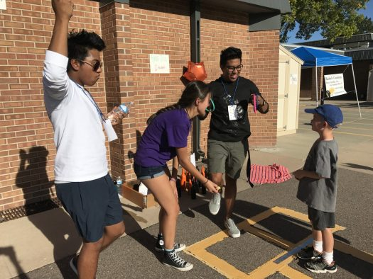 Seniors Kellie Roth, Tucson and Turner DeShon help a kid with the ring toss.