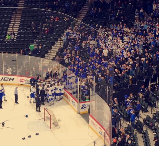 Minnetonka's hockey team celebrates with their student section after winning the championship game.