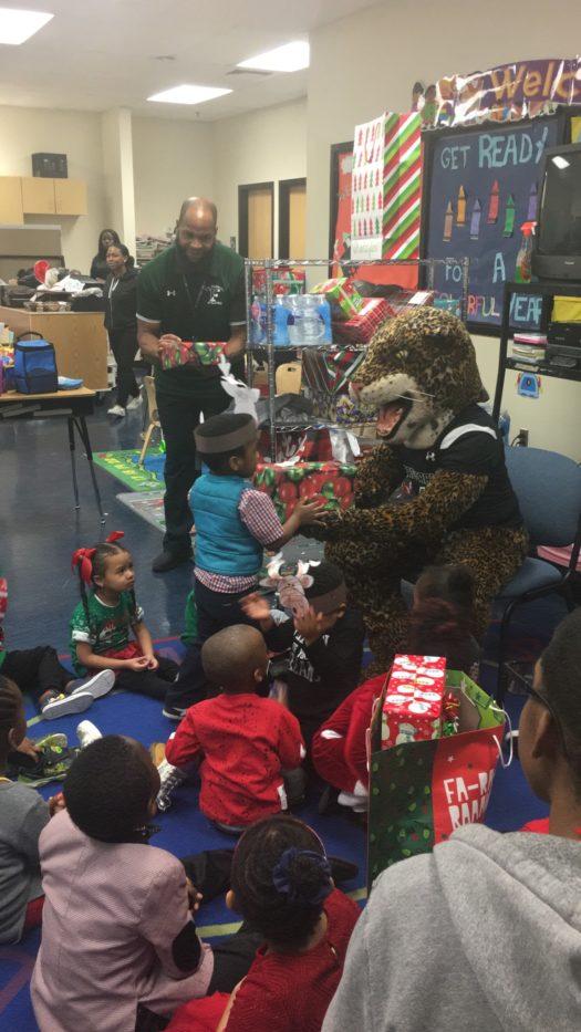 Jaguar hands Preschoolers Holiday Gifts