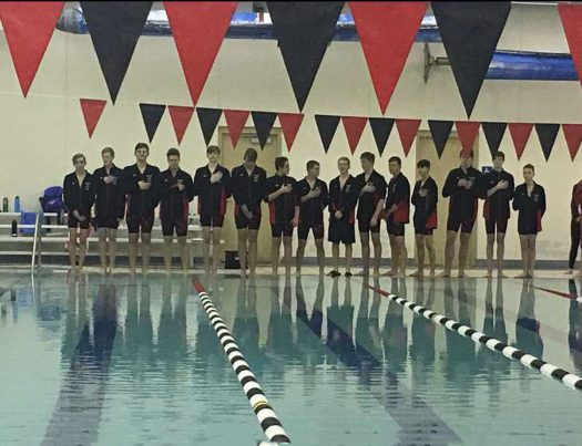 The Boy's Swim Team listening to the National Anthem before a home swim meet.