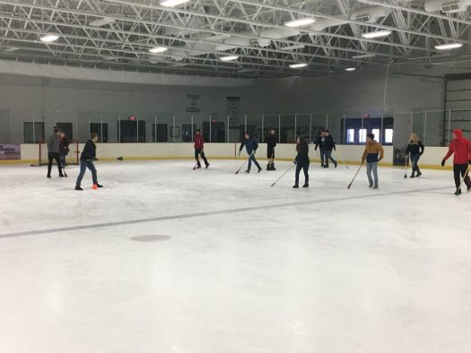 A Challenge class battles for a point during broomball.