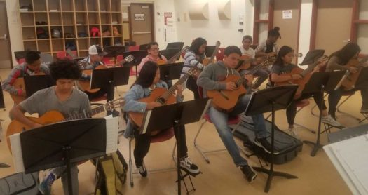 Our guitar class practices playing a song.