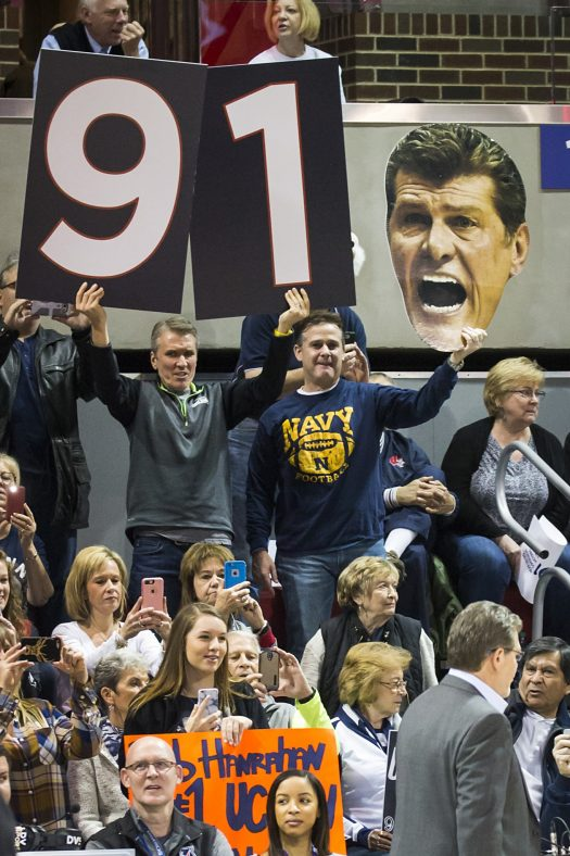 Fans support UConn head coach Gene Auriemma as he ties the NCAA record for wins.