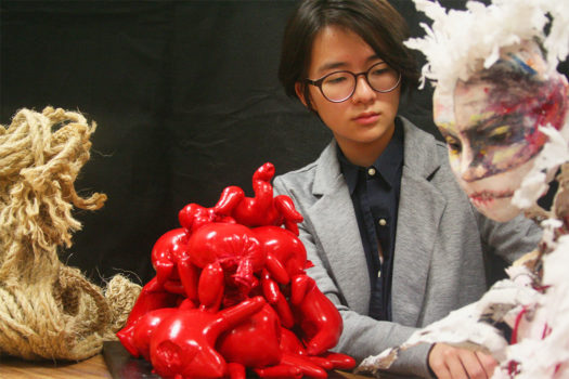 Jean Lee observes her sculptures at an art class showing.