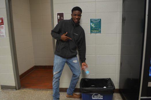 Student De Jones, Junior, putting a bottle in the E-wing recycle bin.