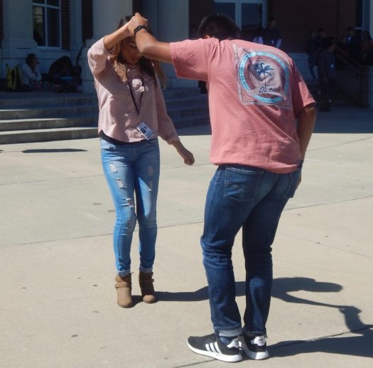 Students dancing to performing students in the courtyard.