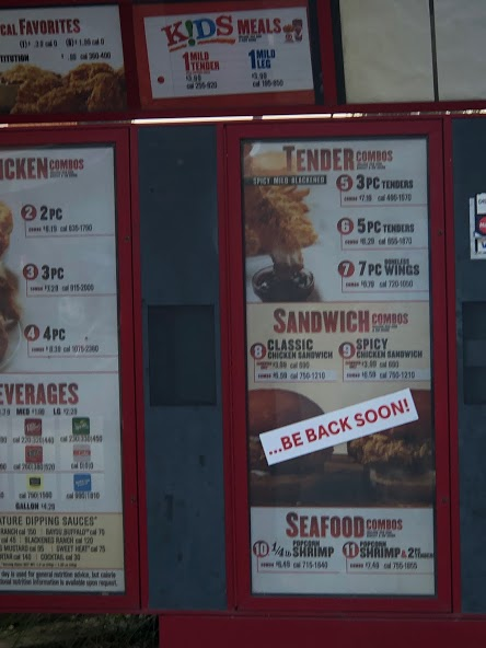 A sign on the Popeye's drive through menu informs customers the chicken sandwich will be back soon.