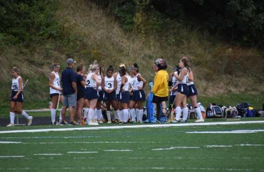 The Varsity Field Hockey team huddled up, halftime.