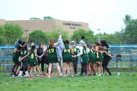 Lacrosse team pictured in a group huddle