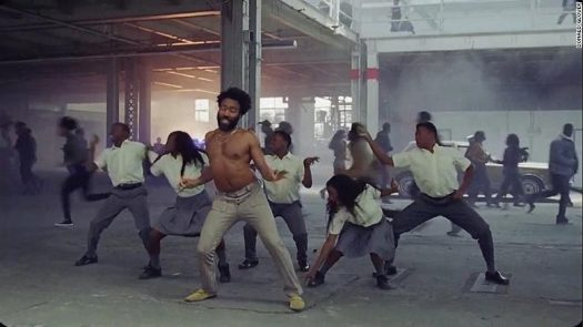As a group of kids dance with Gambino, the world behind them are in chaos