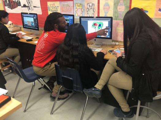 Mr. Tre helps students work on their graphic design project.
